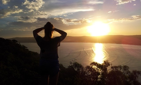Individual counselling client looking out from a hill at sunset over Umina Beach